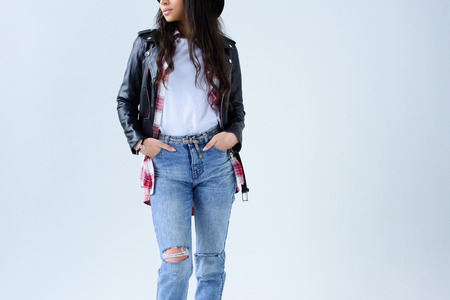 Cropped shot of stylish young woman in leather jacket and jeans isolated on grey Banque d'images