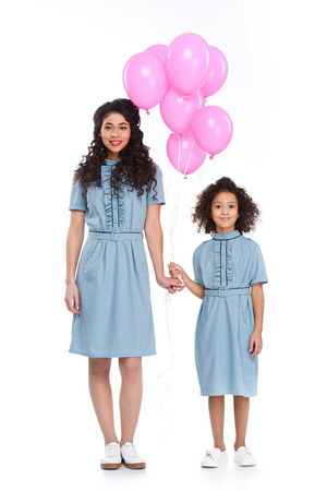 Mother and daughter in similar dresses with bunch of pink balloons isolated on white 스톡 콘텐츠