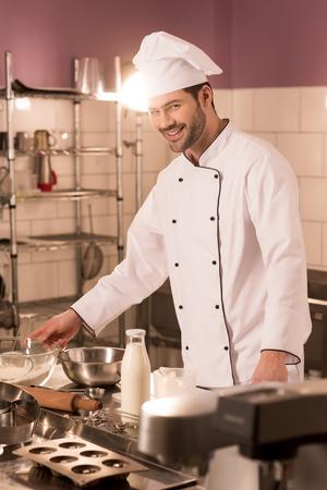 Smiling confectioner standing at counter in restaurant kitchen Zdjęcie Seryjne