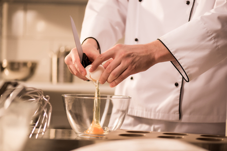 Cropped shot of confectioner breaking egg into bowl while making dough