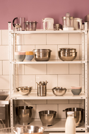 Close up view of various kitchen supplies on shelves in restaurant kitchen