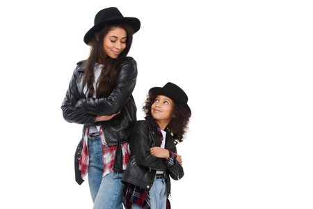 Stylish mother and daughter in similar clothes standing back to back isolated on white
