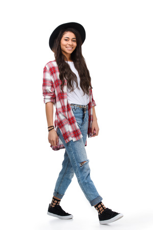 Beautiful walking young woman in stylish plaid shirt isolated on white Archivio Fotografico - 112272029