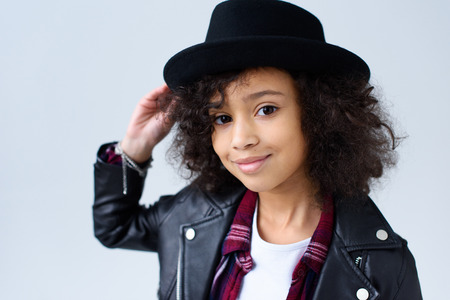 Close-up portrait of adorable little child in leather jacket and hat looking at camera isolated on grey