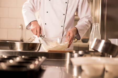 partial view of confectioner with whisk making dough in restaurant kitchen
