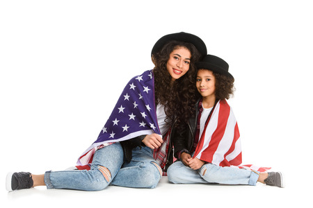 mother and daughter covered in usa flag sitting on floor isolated on white
