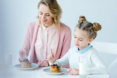 selective focus of mother and daughter having breakfast together at table Stock Photo