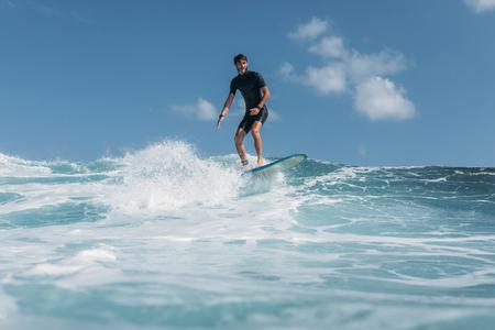 man surfing wave on surf board in ocean