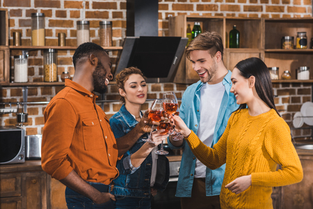 happy young multiethnic friends clinking wine glasses at home