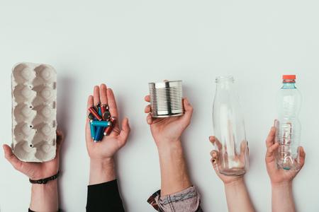 Teilansicht einer Gruppe von Menschen, die verschiedene Arten von Müll isoliert auf Grau hält