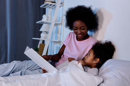 African american mother reading daughter in evening