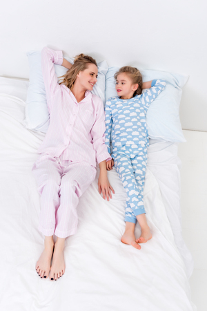 High angle view of mother and daughter lying on bed at home Archivio Fotografico