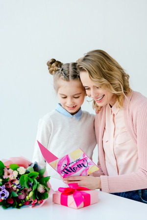 Cheerful mother and daughter reading i love you mom greeting postcard together, mothers day concept Banco de Imagens