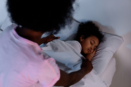 African american mother covering sleeping daughter with blanket at home Stockfoto
