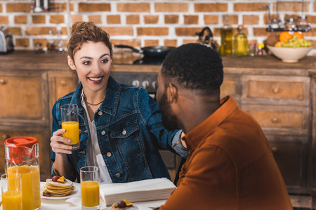 Beautiful happy young multiethnic couple having breakfast together at home