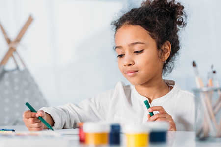 Adorable African american kid painting with felt pens at home