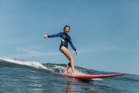 Sportswoman gesturing and riding wave on surf board in ocean