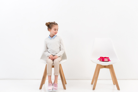 adorable child sitting on chair and looking at present on another chair on white Stock Photo