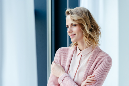 Portrait of beautiful thoughtful woman in pink blouse and jacket looking away Фото со стока