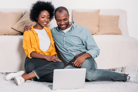 Smiling African american couple watching film on laptop at home Stock Photo