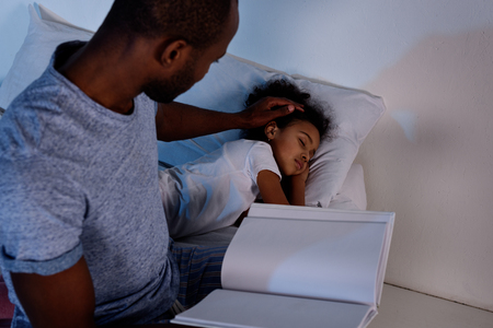 African american father holding book and palming sleeping daughter Stok Fotoğraf