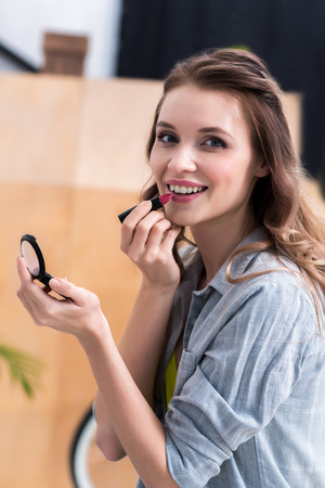 Beautiful young woman applying makeup and smiling at camera Foto de archivo