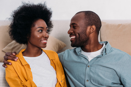 Laughing African american couple looking at each other at home