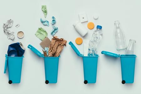 Draufsicht auf Mülleimer und sortierten Müll einzeln auf Grau, Recycling-Konzept