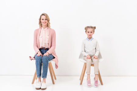 Mother and daughter sitting on chairs and looking at camera on white