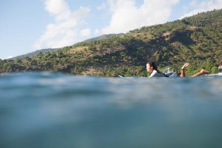woman lying on surf board in ocean, coastline on background 写真素材