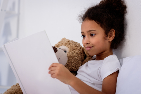 adorable african american kid reading book and hugging teddy bear at home Stock Photo
