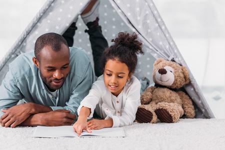 Père et fille afro-américains lisant un livre ensemble à la maison