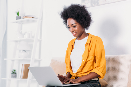 African american woman using laptop at home