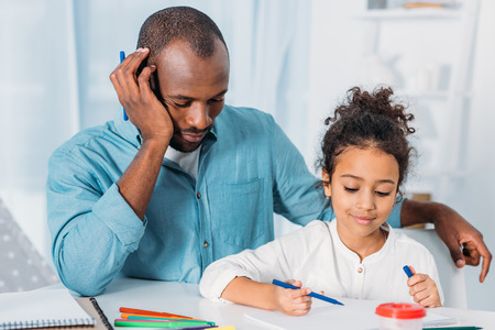 African american father napping and daughter drawing at home
