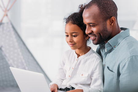 Side view of happy african american father and daughter using laptop at home Stock Photo