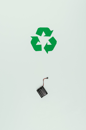 Top view of recycle sign and accumulator isolated on grey