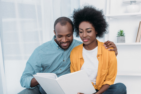 African american couple reading book together at home
