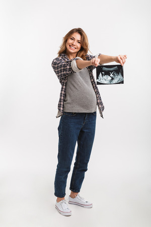 Smiling pregnant woman showing ultrasound scan in hands isolated on grey Foto de archivo - 112272777