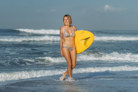 Beautiful girl with surf board walking on beach with waves