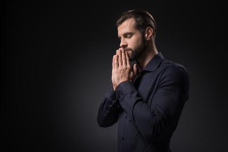 side view of man praying isolated on black Standard-Bild