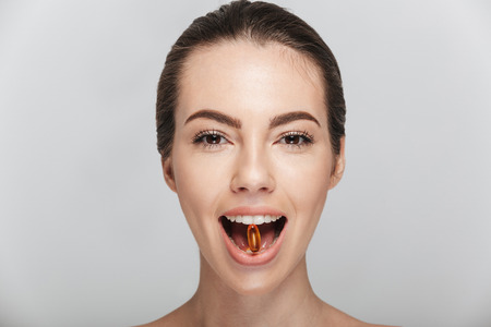 young woman with fish oil capsule in mouth isolated on white