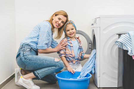 mother and daughter looking at camera while putting clothes into washing machine at home Standard-Bild - 111736294