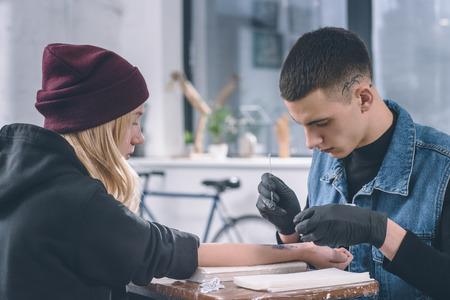 Tattoo artist in gloves working on female arm piece in studio