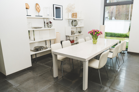 view of stylish empty dining room with bouquet of tulips on table
