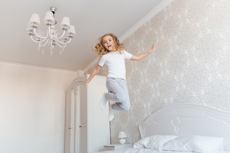 smiling child jumping on bed and looking at camera