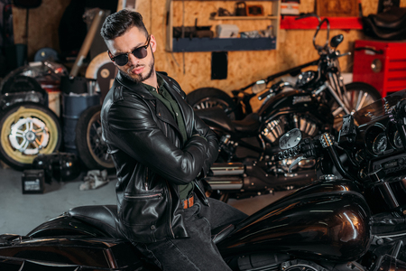 handsome young man in sunglasses and leather jacket on bike at garage