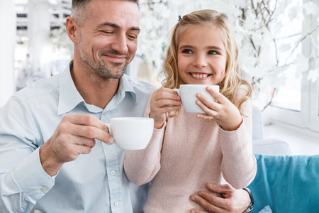 young father and daughter drinking tea in cafe Banco de Imagens
