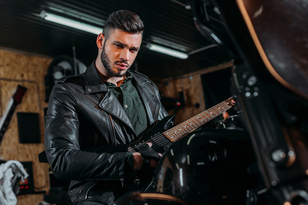handsome young man playing guitar while sitting on bike at garage Stock Photo
