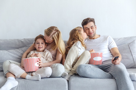 loving family watching movie on couch at home with popcorn