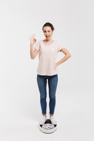 young woman showing okay sign while standing on scales isolated on white Stock Photo - 111736387